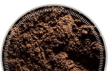 Photo of dark brown test dust in a round dish